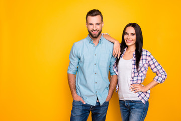 Portrait with copyspace of trendy cool couple in pants casual shirts looking at camera isolated on vivid yellow background. Advertisement concept Fotoväggar