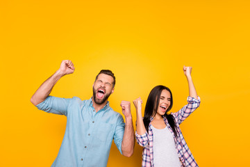 Portrait of crazy man couple full of happiness yelling loudly holding raised arms keeping eyes closed celebrating victory isolated on vivid yellow background