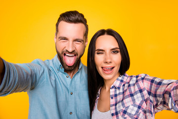 Self portrait of funny comic couple shooting selfie on front camera gesturing tongue out blinking with one eye isolated on vivid yellow background. Rest relax leisure concept