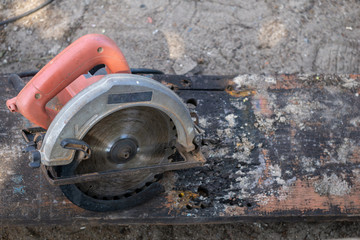 An electrical portable  circular saw with orange handle on the old and dirty plank
