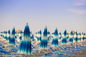 Rimini. Italy. Beach umbrellas on blue clear sky background.