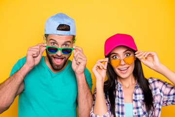 Head shot portrait of surprised glad students with unexpected unbelievable expression looking out eyewear with wide open mouth eyes isolated on vivid yellow background