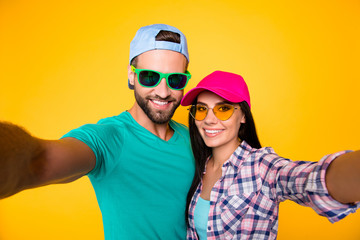 Self portrait of stylish trendy students in modern eyeglasses colorful headwear shooting selfie on front camera having beaming smiles isolated on bright yellow background