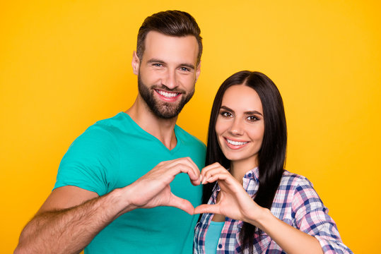 Portrait of romantic lovely couple making heart figure with fingers looking at camera isolated on vivid yellow background. Harmony idyllic understanding concept