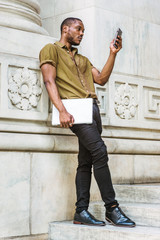 Young African American Man studying in New York, wearing green short sleeve shirt, black pants, leather shoes, carrying laptop computer, standing against white marble wall, texting on cell phone..