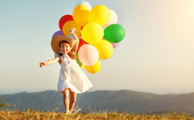 happy child with balloons at sunset in summer