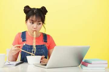 Asian woman sitting at the table with laptop and eating noodles