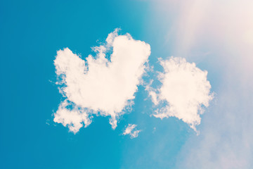 White fluffy clouds in the form of heart and sky, background.