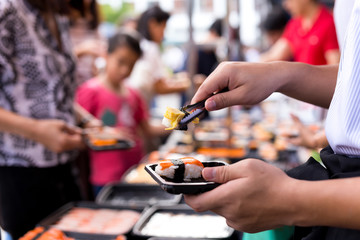 Hand picking sushi roll from food stall at event street market