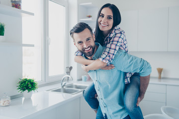Portrait of cheerful joyful couple, handsome man carrying on back pretty woman standing in modern white kitchen looking at camera enjoying tome together