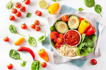 vegan buddha bowl. healthy lunch bowl with avocado, tomato, bell peppers, quinoa and salsa