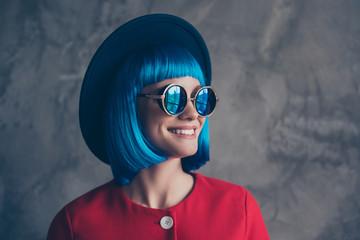 Portrait of toothy modern girl in headwear eyewear blue wig looking away isolated on grey background