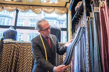 Senior tailor looking at ties in tailors shop