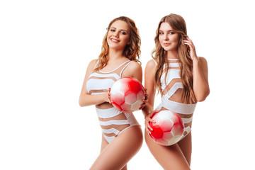 Pretty bikini models holding red balls in studio