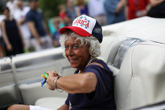 A woman throws candies from a vintage car as she rides on Main Street during the annual Fourth of July parade in Barnstable Village