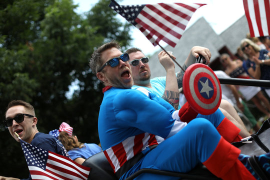 A man in Captain America costume rides down Main Street during the annual Fourth of July parade in Barnstable Village