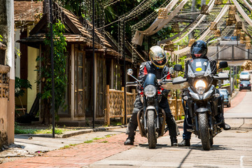 Men on scrambler motorbikes reading road map in alley, Mae Hong Son, Thailand