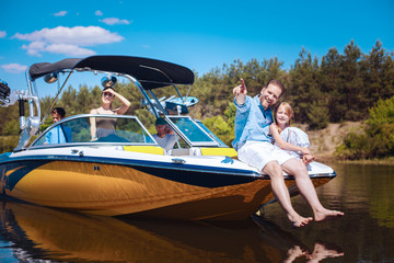 Unforgettable weekend. Pleasant young family enjoying their weekend on a motorboat while father and his little daughter discussing their final destination on boat bow
