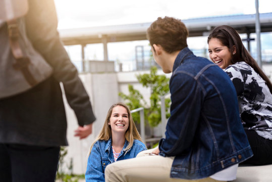Four young adult students chatting on college campus