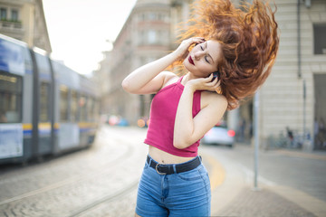 Beautiful girl listening music and dancing in the street