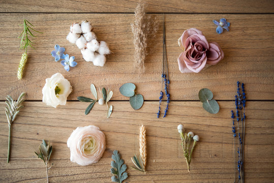 Still life of pastel coloured flower heads, flower stems and leaves on wood, overhead view