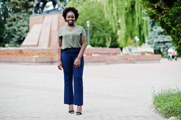 African girl posed at street of city wear on green blouse and blue pants.