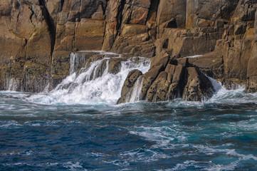 Vue sur la parois d'une falaise avec la vague qui se retire sur la mer en Bretagne
