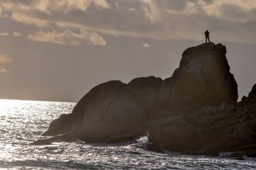 Silhouette d'un homme perché sur un rocher en fin de journée en Bretagne