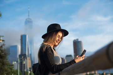 Portrait of woman looking at mobile phone smiling, New York, USA