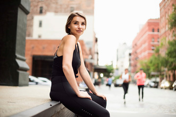 Portrait of woman sitting on wall looking at camera, New York, USA