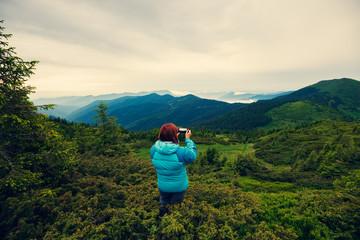 Adventurer female making a photo using a smartphone