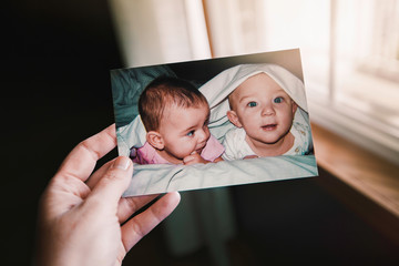 Mother holding photograph of twin baby girl and boy, close up of hand, personal perspective