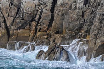 Vue sur la parois d'une falaise avec la vague qui se retire sur la mer