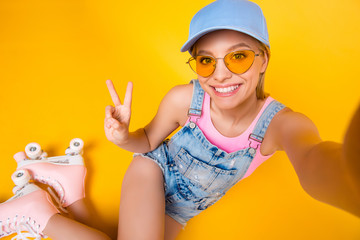 Self portrait of positive toothy girl shooting selfie on front camera wearing roller skates gesturing v-sign with hand isolated on yellow background, fitness workout athletic sport concept