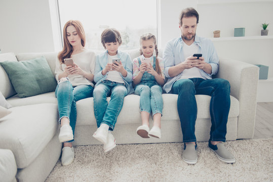 Portrait of family with two kids having holding smart phone electronic device in hands texting sms using wi-fi 5G internet checking email searching contact. Apps concept