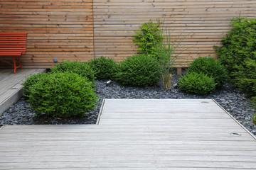Moderne Garten- und Terrassengestaltung: Terrasse aus Holz und Pflanzen im pflegeleichten Schotterbett vor einer Holzwand