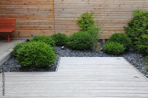 Moderne Garten  Und Terrassengestaltung: Terrasse Aus Holz Und Pflanzen Im  Pflegeleichten Schotterbett Vor Einer