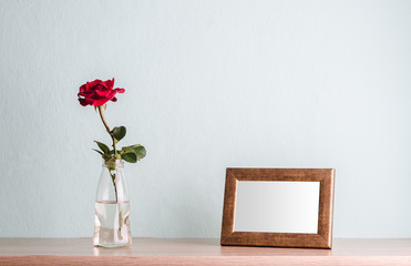 Empty photo frame and a rose in a vase