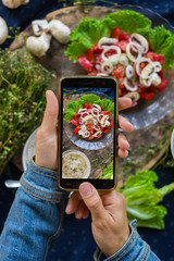 Woman hands take smartphone food photo of vegetables salad with tomatoes. Phone food photography for social media or blogging in popular and trendy top view style. Raw vegan vegetarian meal concept.