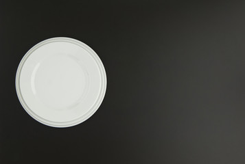 ceramic kitchen plate on black background, top view
