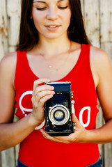 young beautiful brunette girl in red shirt and jeans shorts posing with a camera on the rustic wooden background. making photos, taking pictures, woman, photographer,vintage camera, outdoor portrait