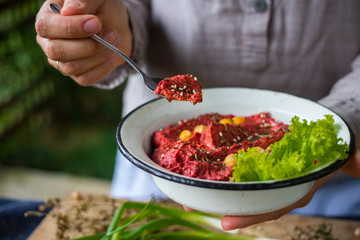 Woman hands holds spicy red beetroot Israeli chickpea hummus with herbs and covered with olive oil. Traditional mediterranean food used with vegetables. Vegan vegetarian healthy food.