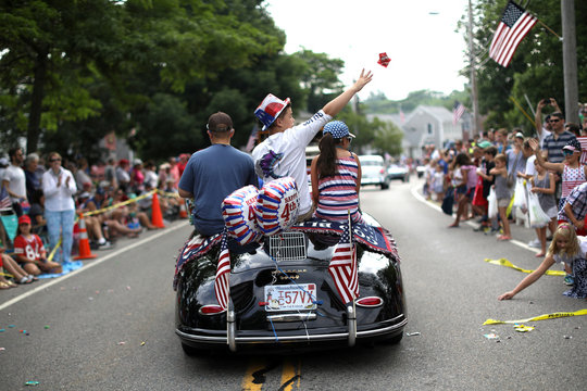 A boy throws candies from a vintage car as he rides on Main Street in the annual Fourth of July parade in Barnstable Village