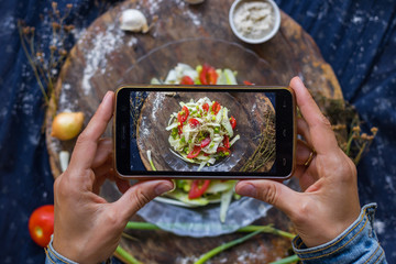 Woman hands take smartphone food photo of raw vegan zucchini spaghetti. Phone food photography for social media or blogging in popular and trendy top view style. Raw vegan vegetarian meal concept.