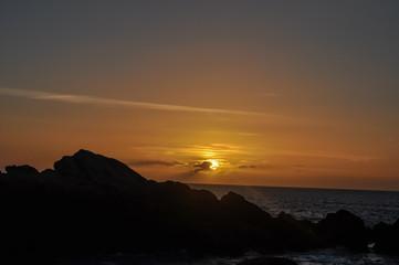 Couché du soleil sur l'océan atlantique avec les silhouettes de rochers en premier plan