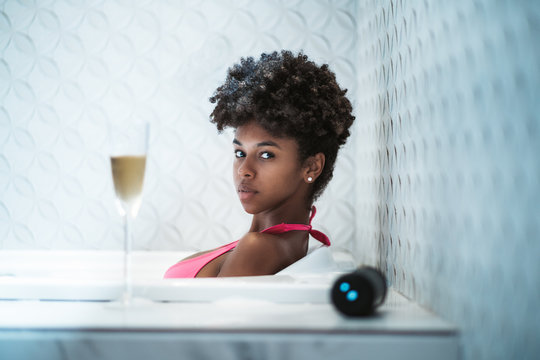 Portrait of a charming young African-American girl in a bathing suit laying and relaxing in the bath with the glass of white wine and wireless speaker in front in a defocused foreground
