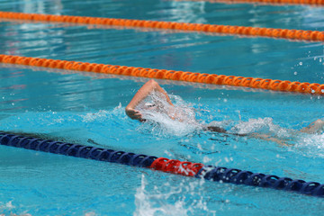 Swimmer swims free style, front crawl or forward crawl stroke in a swimming pool for competition or race
