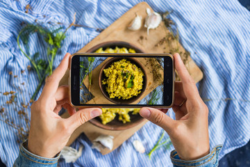 Woman hands take smartphone food photo of cauliflower vegan rice. Phone food photography for social media or blogging in popular and trendy top view style. Raw vegan vegetarian meal concept.