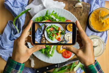 Woman hands take smartphone food photo of vegan spring rolls. Phone food photography for social media or blogging in popular and trendy top view style. Raw vegan vegetarian meal concept.