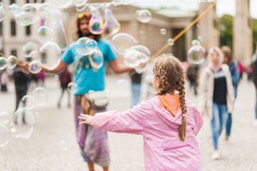 Street performer, busker, entertaining the crowd in front of the Brandenburg Gate in Berlin on an overcast summer day. Children playing with colorful soap bubbles floating in the foreground.